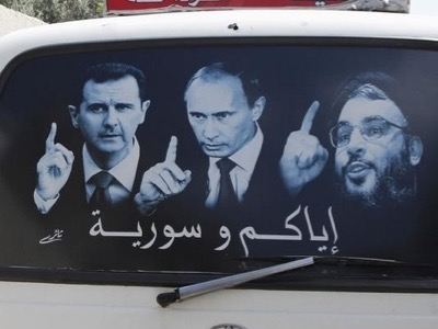 A poster showing Syrian President Assad, Russian President Putin and Lebanese Hezbollah leader Nasrallah is seen on a micro bus in al-Qardahah town, near Latakia city